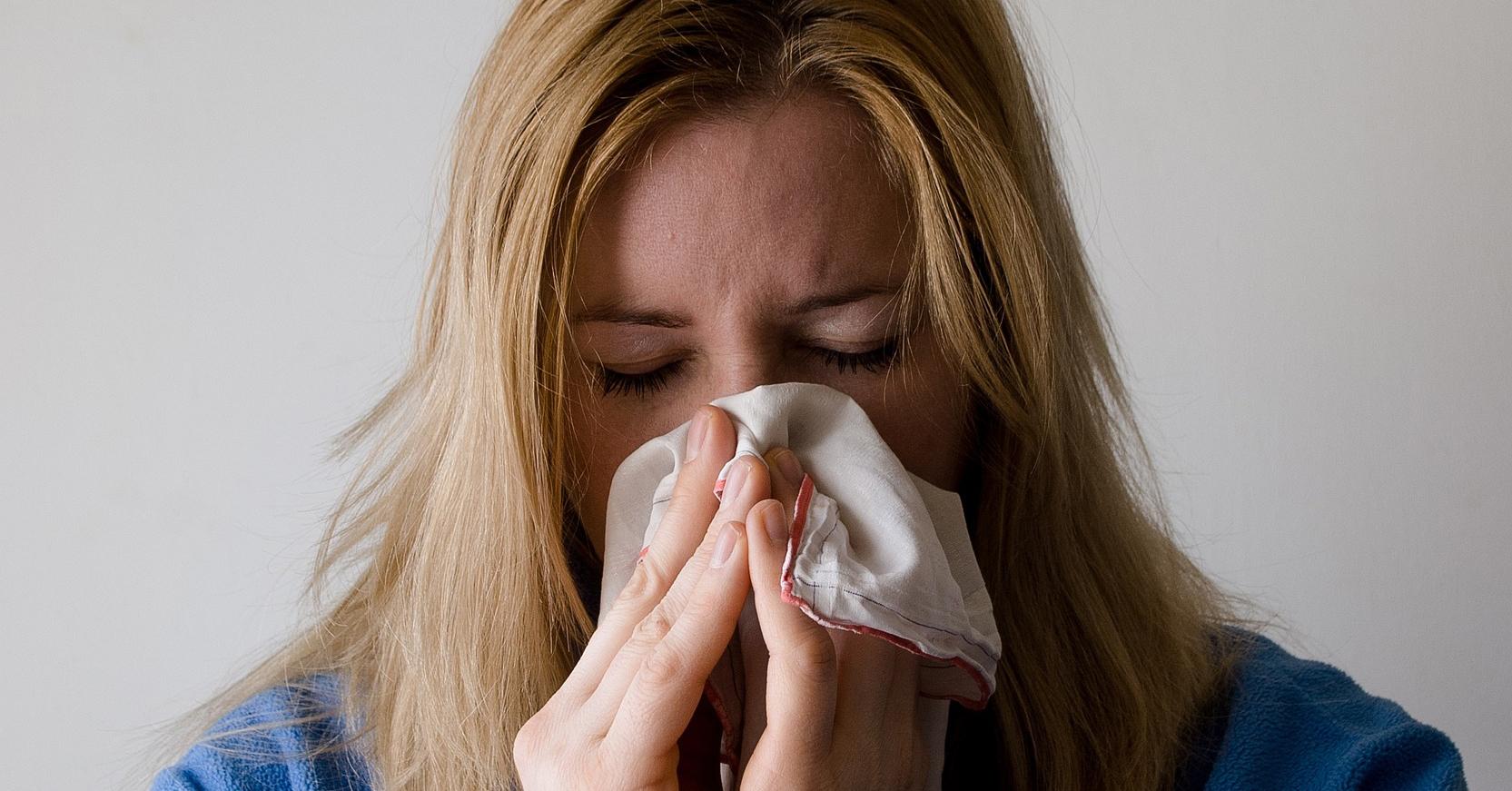 Nemocná žena smrkající do kapesníku